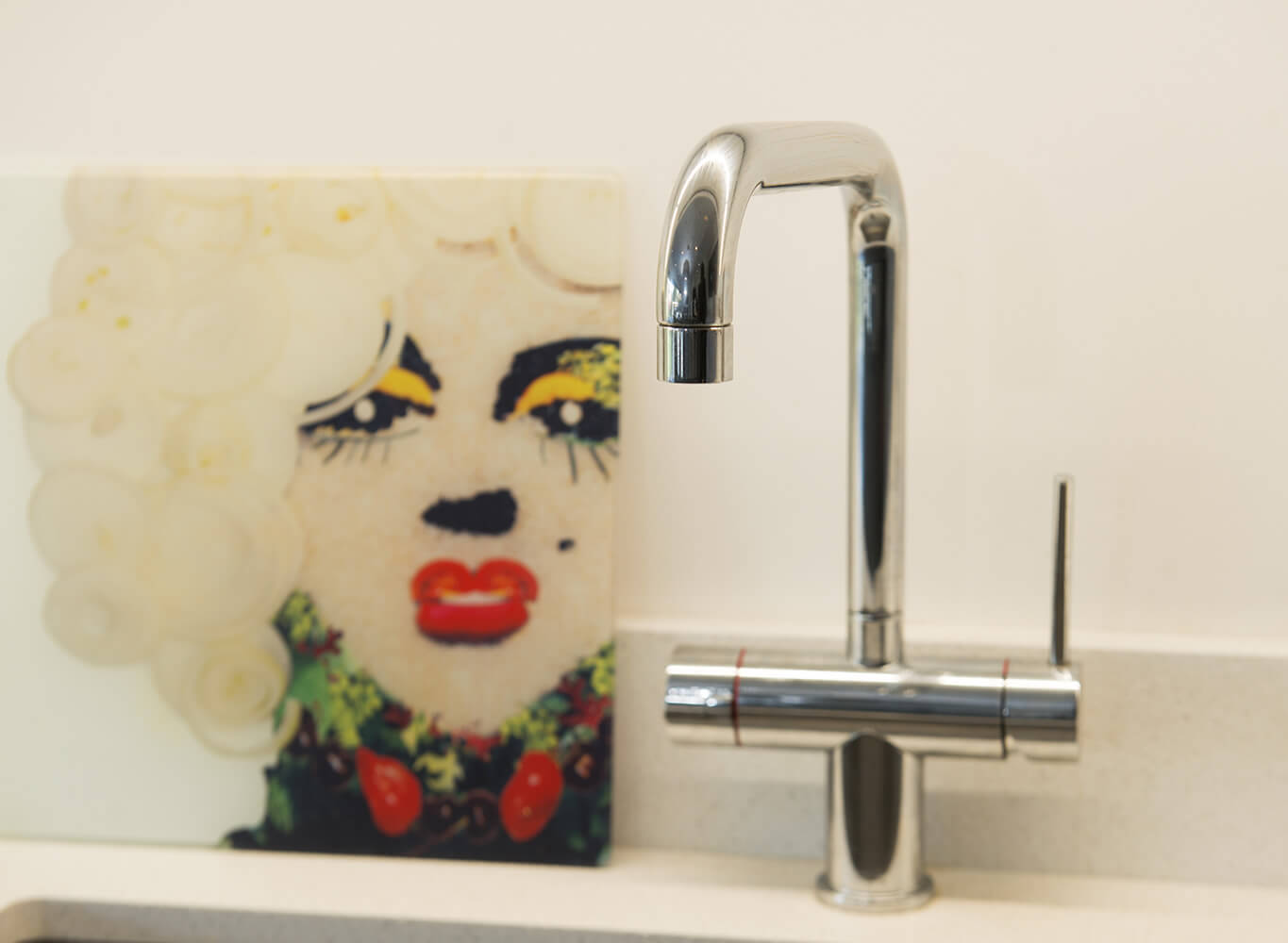 Tap and a sink with a picture next to it close up