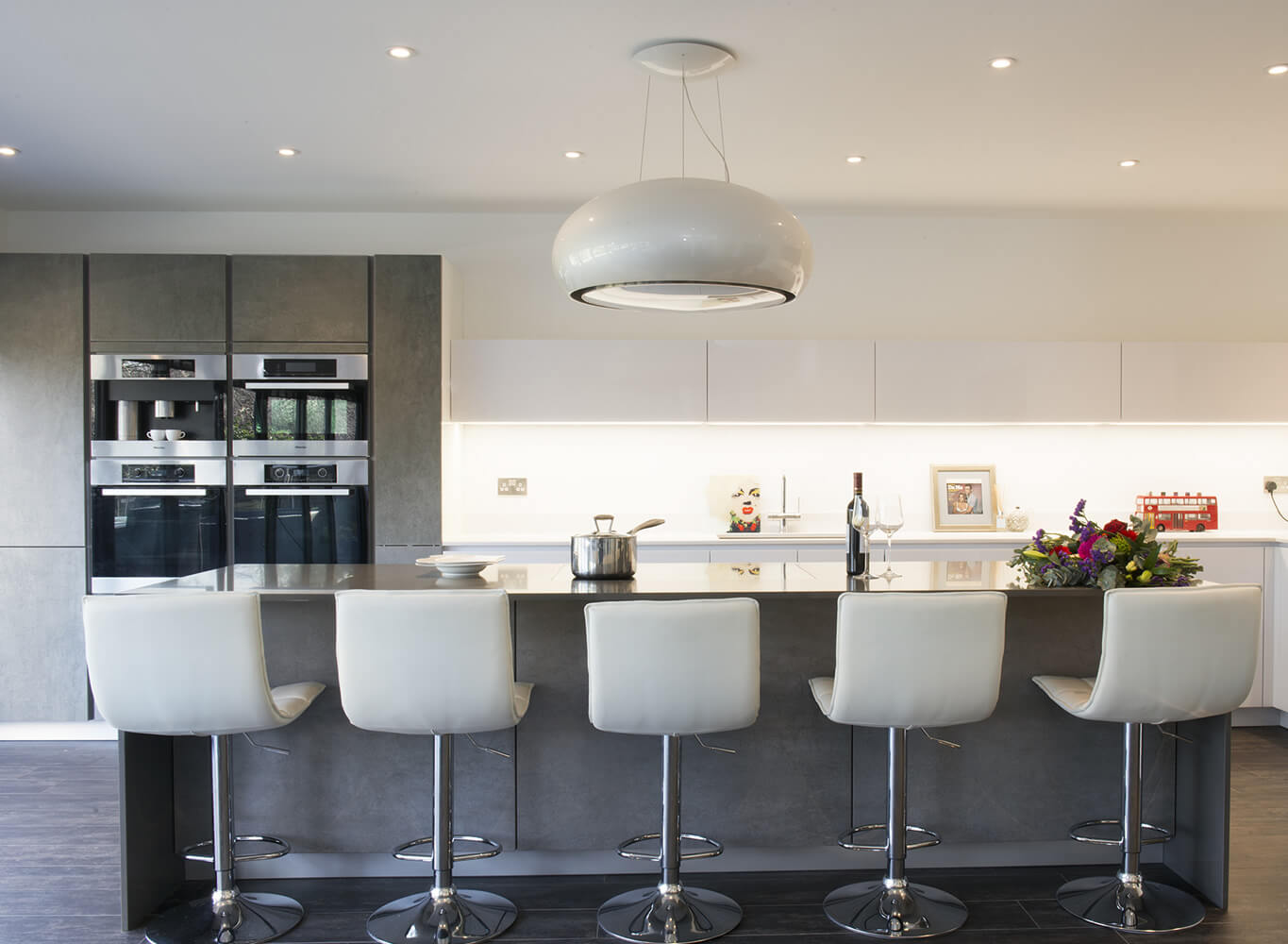Dark kitchen with white bar chairs